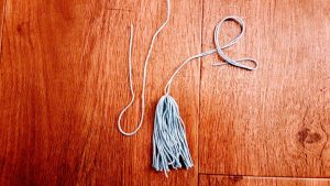 Form a loop with a third piece and wrap the ending around the neck of your tassel.